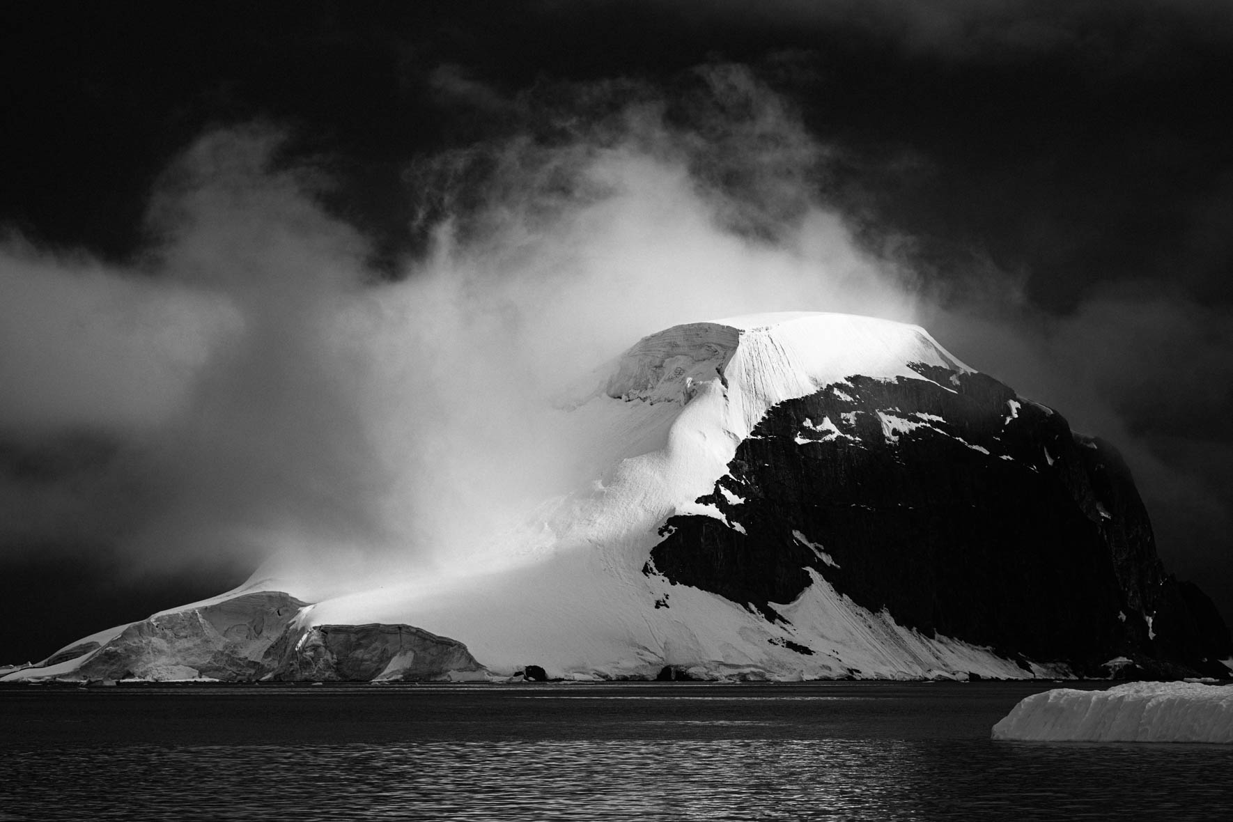 Black and white photo of mountain in the clouds in Antarctica
