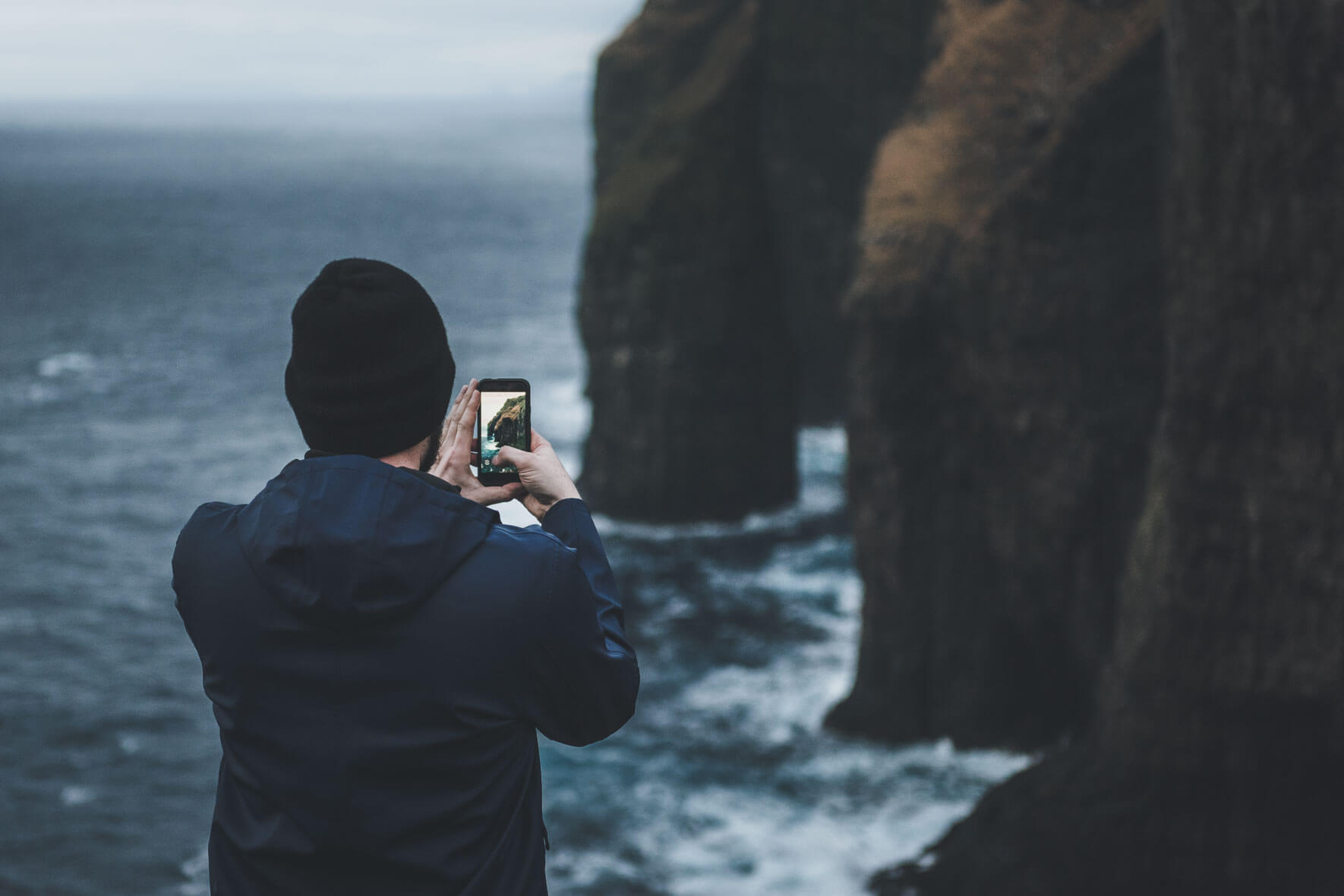 Man taking photo of Ásmundarstakkur sea stack on the Faroe Islands