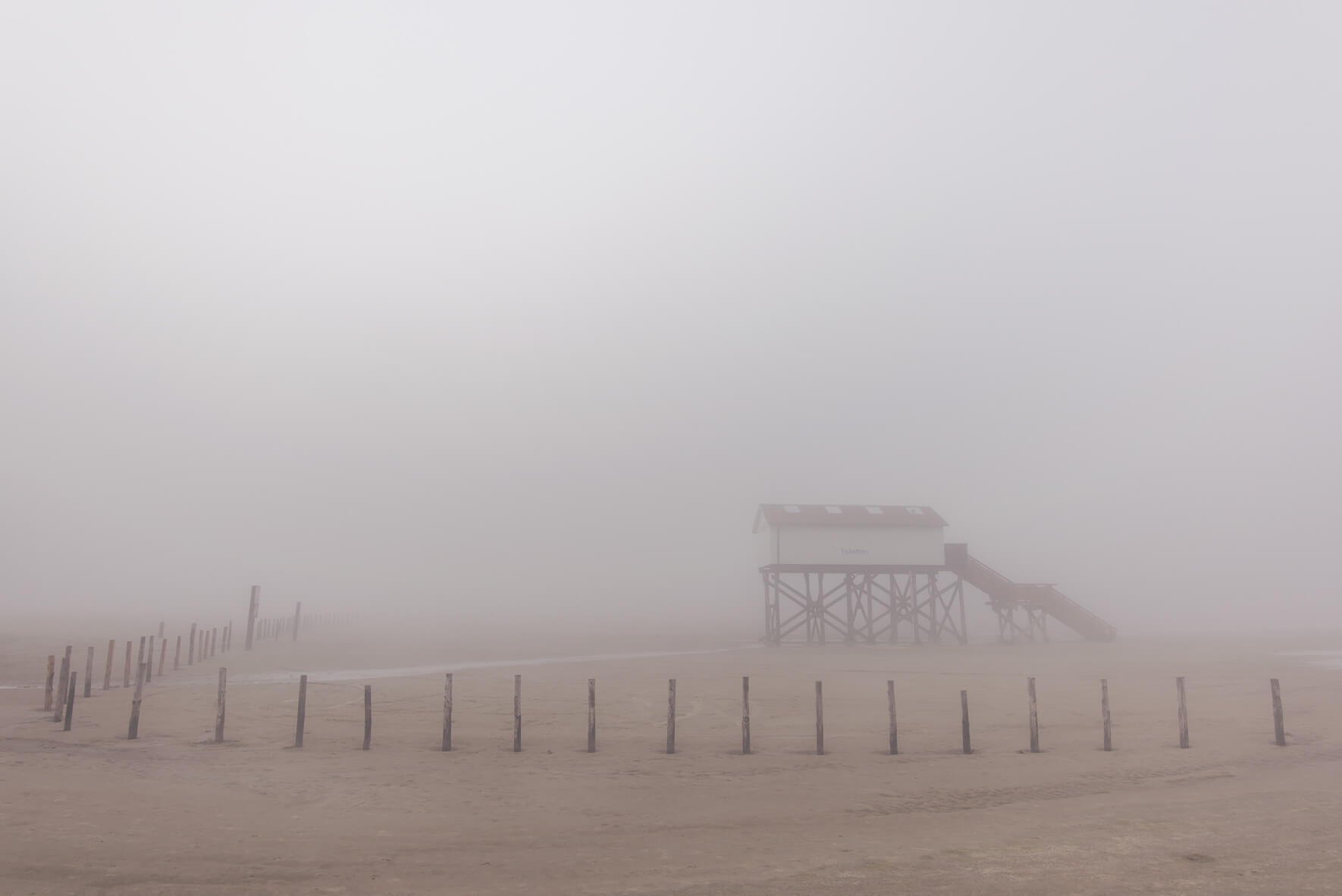 Coastal fog over the beach of Sankt Peter-Ording with a stilt house