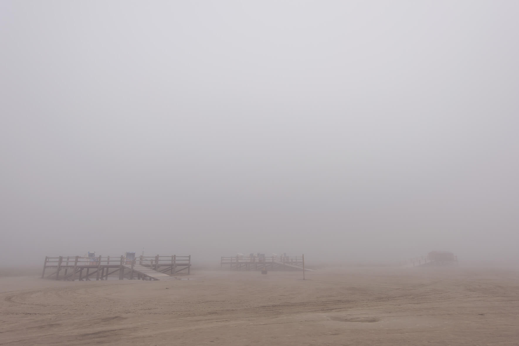 Fog over the beach of Sankt Peter-Ording with beach chairs